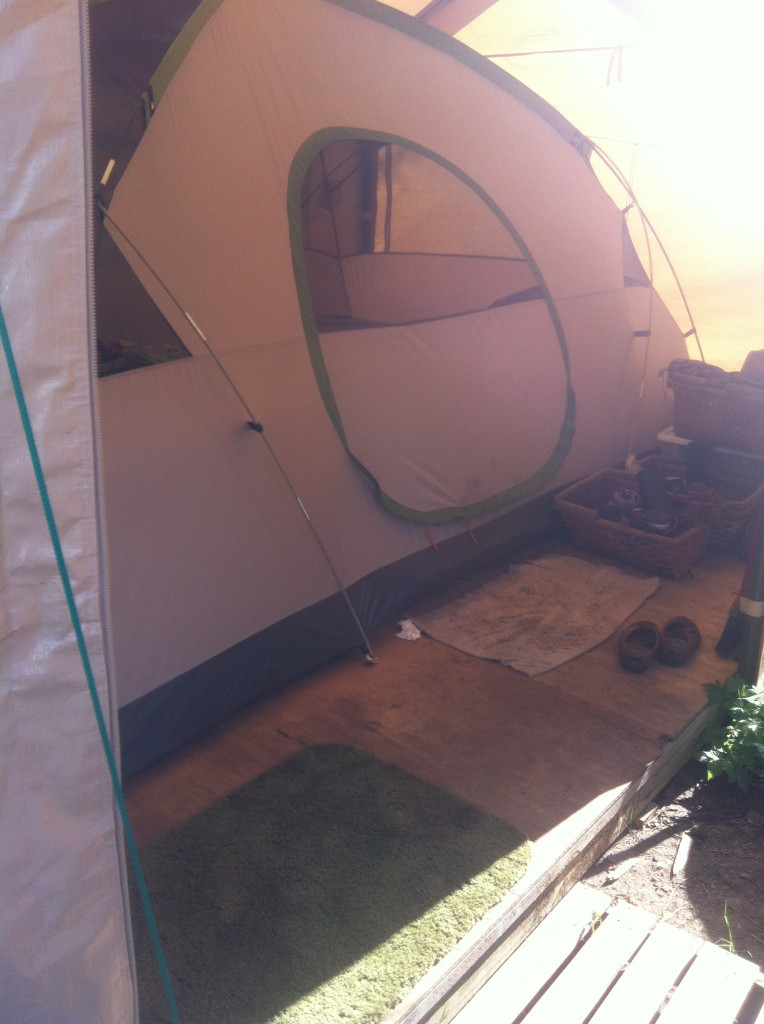 Inside the carport, the tent is up on a raised plywood floor